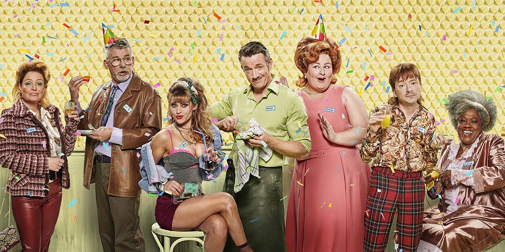 zeven volks geklede types uit het Schaep met feesthoedjes, taart, drankjes en confetti