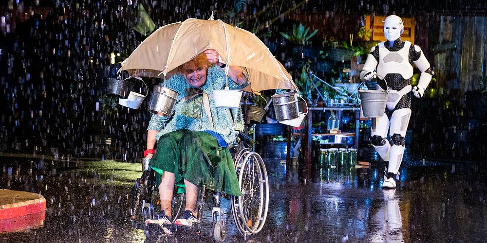 Betty in rolstoel onder paraplu waar metalen emmertjes aan hangen, op de achtergrond komt robot Shiny met een grote emmer aanlopen
