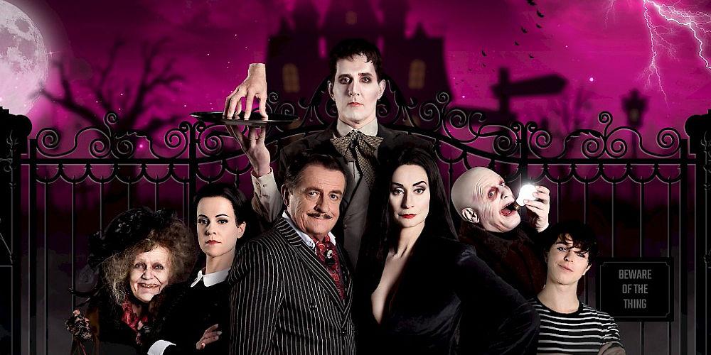 Zes leden van de Addams Familie poseren voor silhouet van griezelig kasteel. Achter hen staat de butler die een dienblad omhooghoudt met een hand erop.